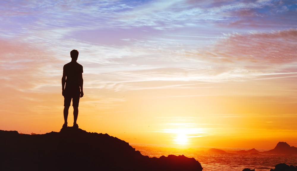Man on cliff looking at sunrise